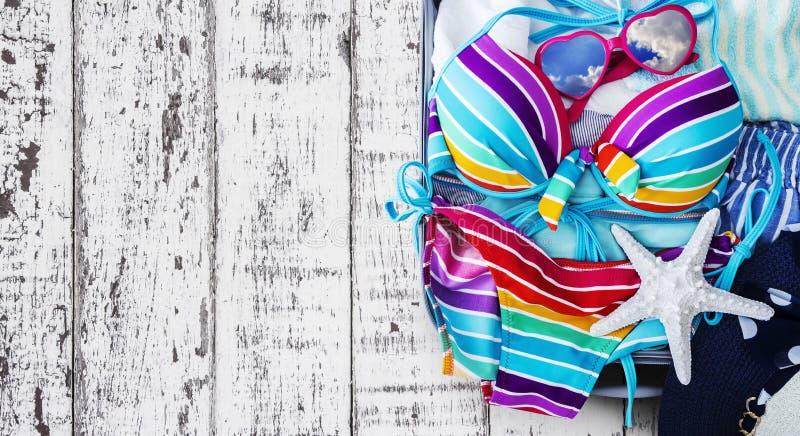 Bikini variopinto e vestiti in bagagli sui precedenti di legno fotografie stock