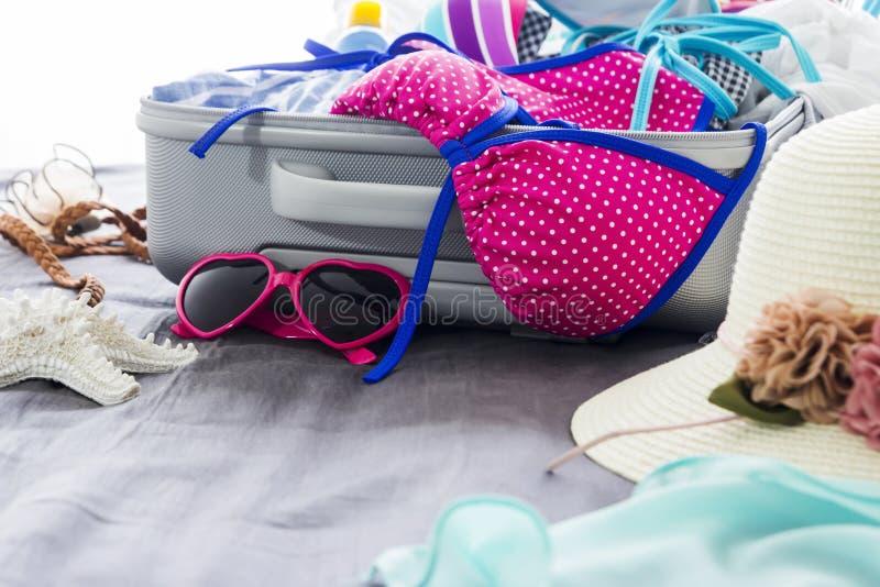 Bikini variopinto e vestiti in bagagli sul letto immagine stock
