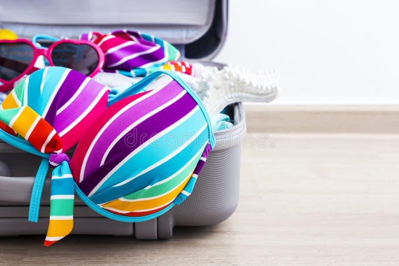 Bikini variopinto e vestiti in bagagli sul pavimento laminato fotografia stock