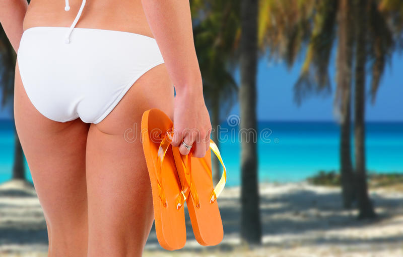 Bikini Woman At The Beach. Slim Woman Wearing A White Bikini Holding Flip Flop Sandals At The Beach stock images