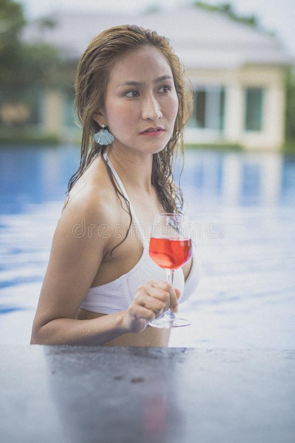 Bikini woman and glass of red beverage in swimming pool stock images