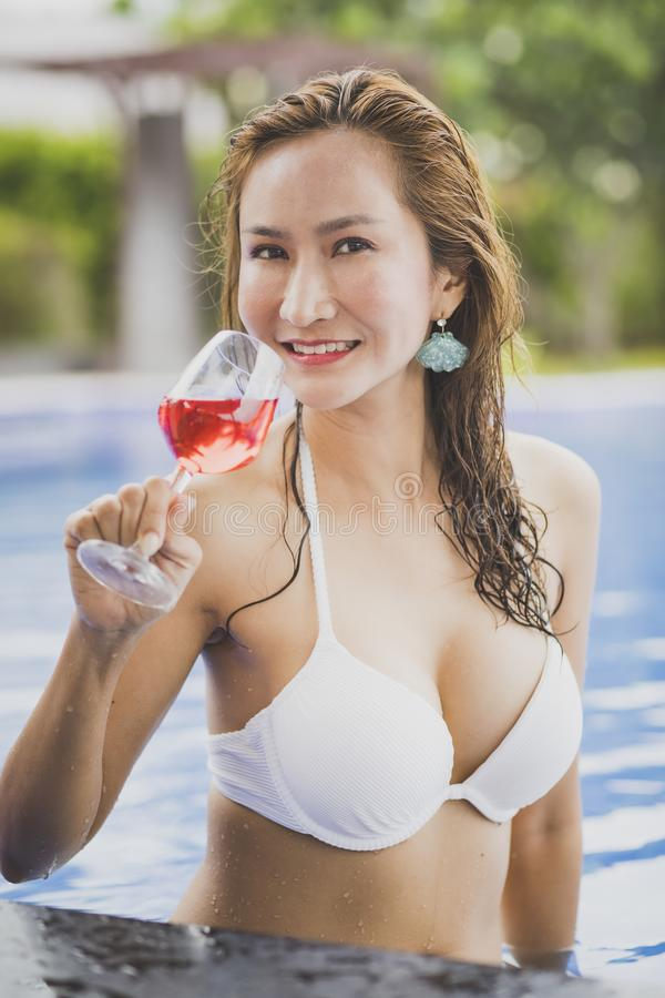 Bikini woman and glass of red beverage in swimming pool stock image