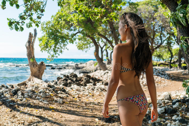 Bikini woman walking relaxing on hawaii beach. Beach woman relaxing walking in shade of trees on exotic hawaiian destination.. Hawaii lifestyle. Casual girl stock photo