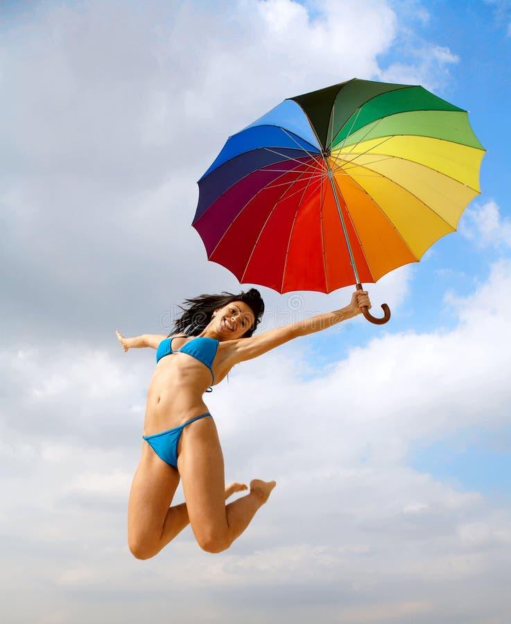 Bikinidame springen mit Regenschirm stockbild