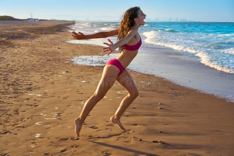 Bikiniflicka som kör till strandkustvattnet arkivbilder