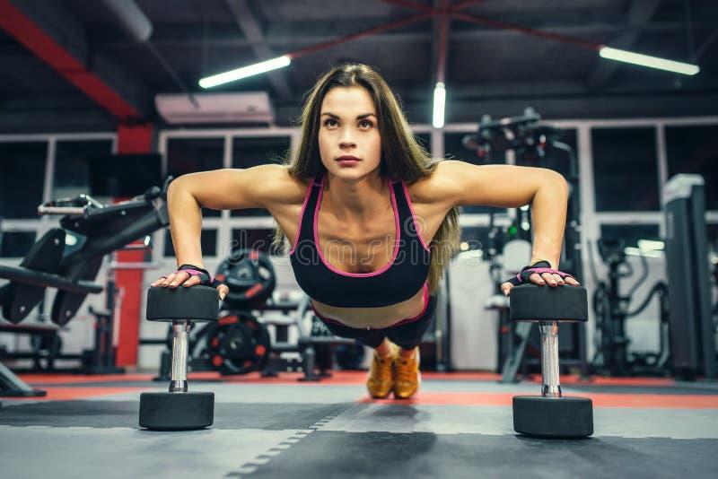 Bikinikonditionflicka som utarbetar med hantlar Idrottsman nenkvinna i sportswearen som gör övning i idrottshall royaltyfria bilder