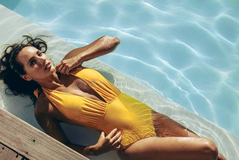 Bikinikvinna som kopplar av i simbassängen royaltyfri foto