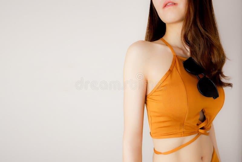 Bikinimodell med sommarbegrepp Den sexiga kvinnan är bröstet i brun underkläder och solglasögon som poserar på Grey Background, s arkivbilder