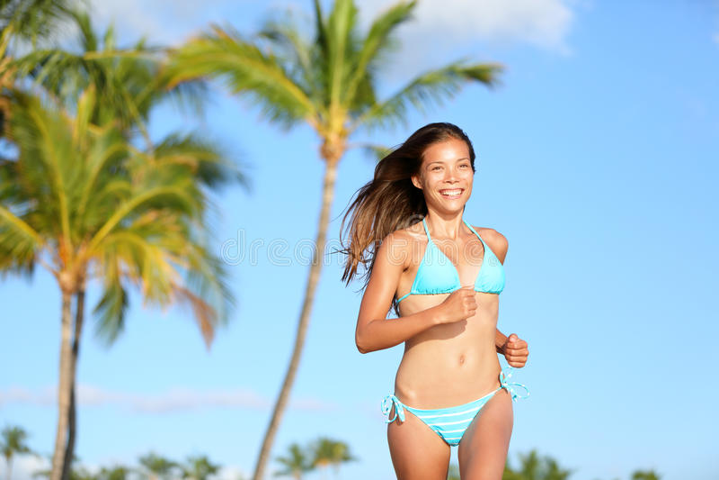Bikinivrouw die bij strand gelukkig glimlachen lopen royalty-vrije stock afbeeldingen