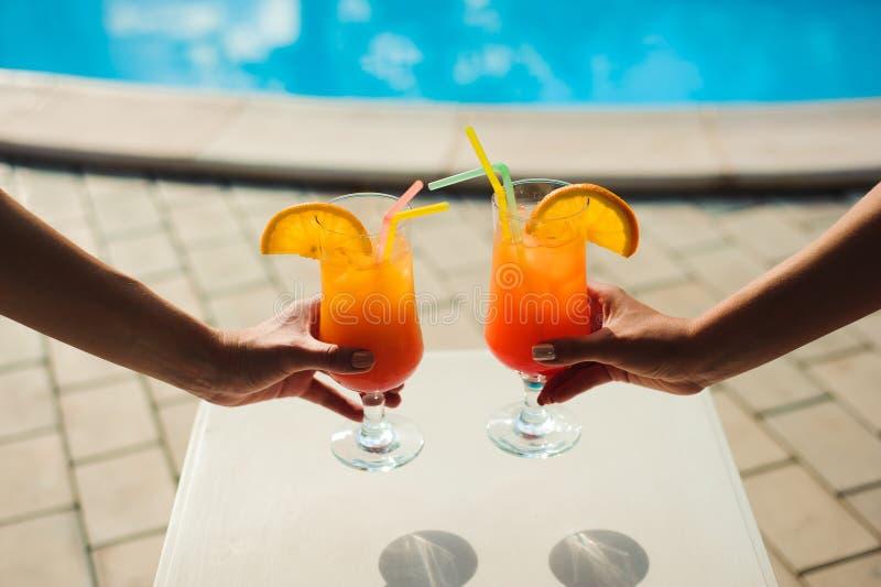 Bikinivrouwen in pool het ontspannen met sap, jonge mooie sexy meisjes die in vakantie bij de zomer bij het zwemmen rusten royalty-vrije stock foto's