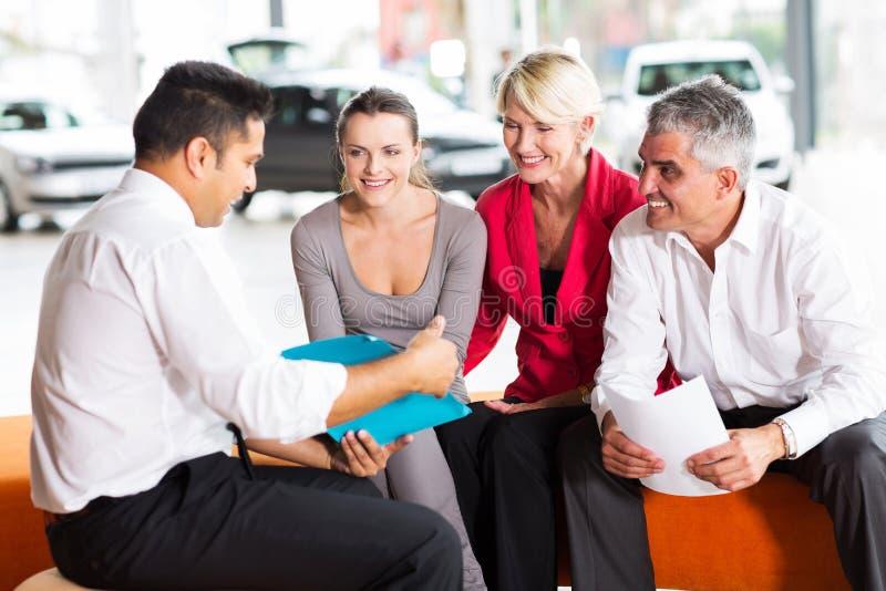 Bilåterförsäljare som förklarar avtalet royaltyfria foton