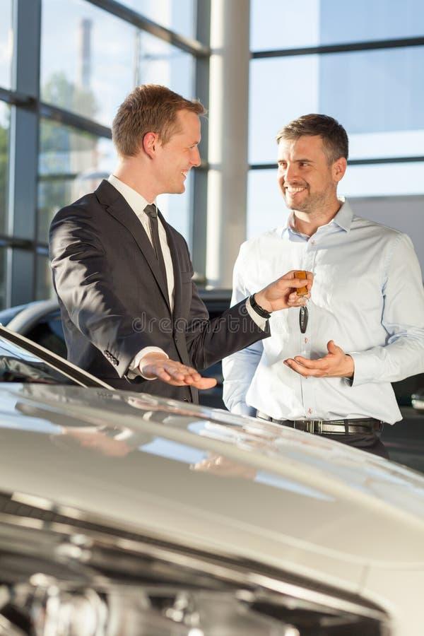 Bilåterförsäljare som ger klienttangenter arkivfoto