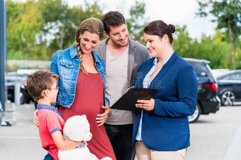 Bilåterförsäljare som råder familjen på den köpande automatiskn arkivbild