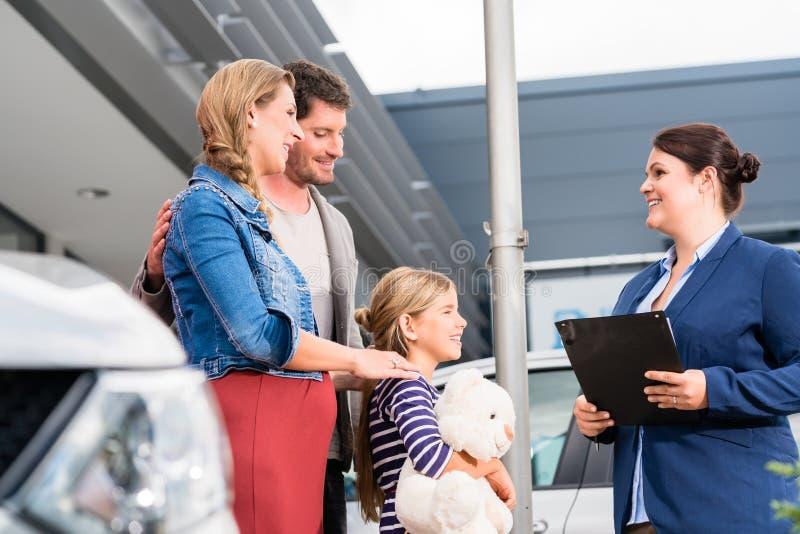 Bilåterförsäljare som råder familjen på den köpande automatiskn arkivfoton