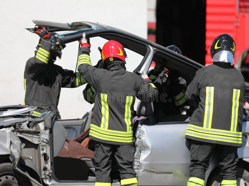 Bil efter vägolycka och brandmännen i handling arkivfoton