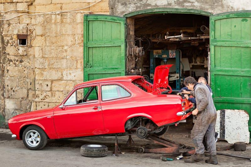 Bil för gammal tappning för reparation för två mekaniker röd arkivfoto