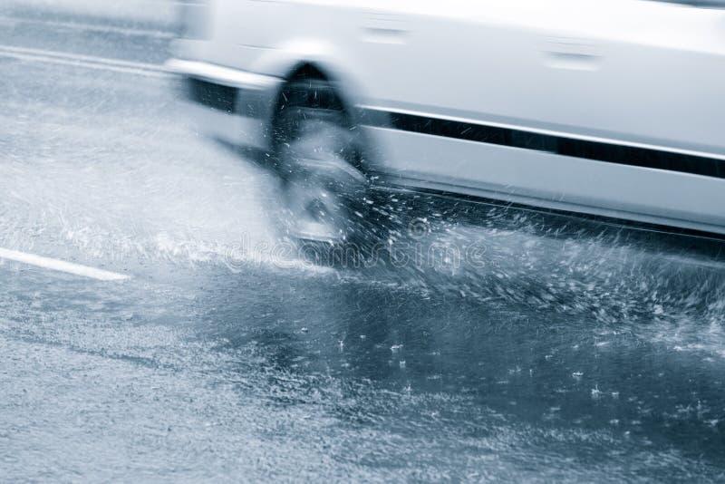 Bil i ett hällregn arkivbilder