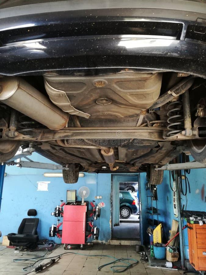 Bil i service som lyfts på hög-kapacitet den hydrauliska stålar Arbetare är i laddning av den bilunderhåll och reparationen royaltyfri foto