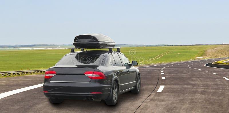 Bil med behållaren för takbagageask för lopp på en väg arkivbild