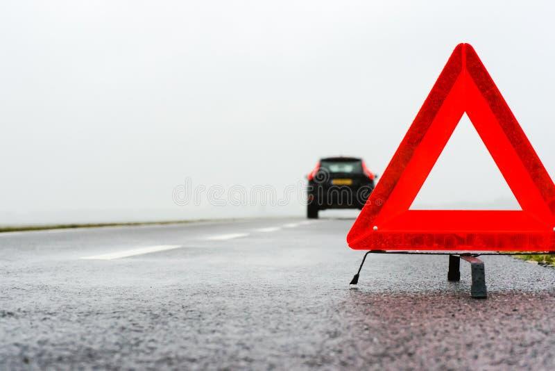 Bil med en sammanbrott i regnet och dimman arkivfoton