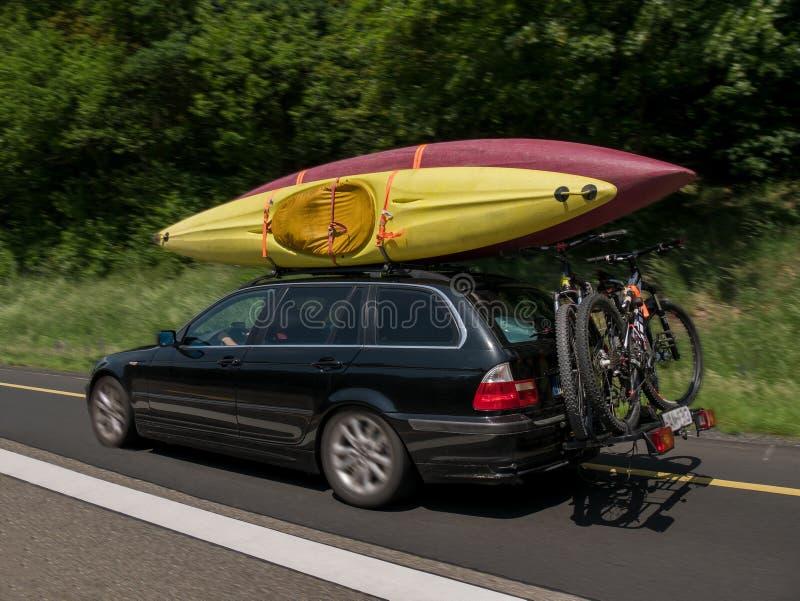 Bil med kajaker på överkanten och cyklar på baksidan som går för ferie royaltyfri fotografi