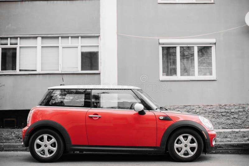 Bil Mini Cooper Parked On Street för röd färg nära bostads- hus royaltyfri foto