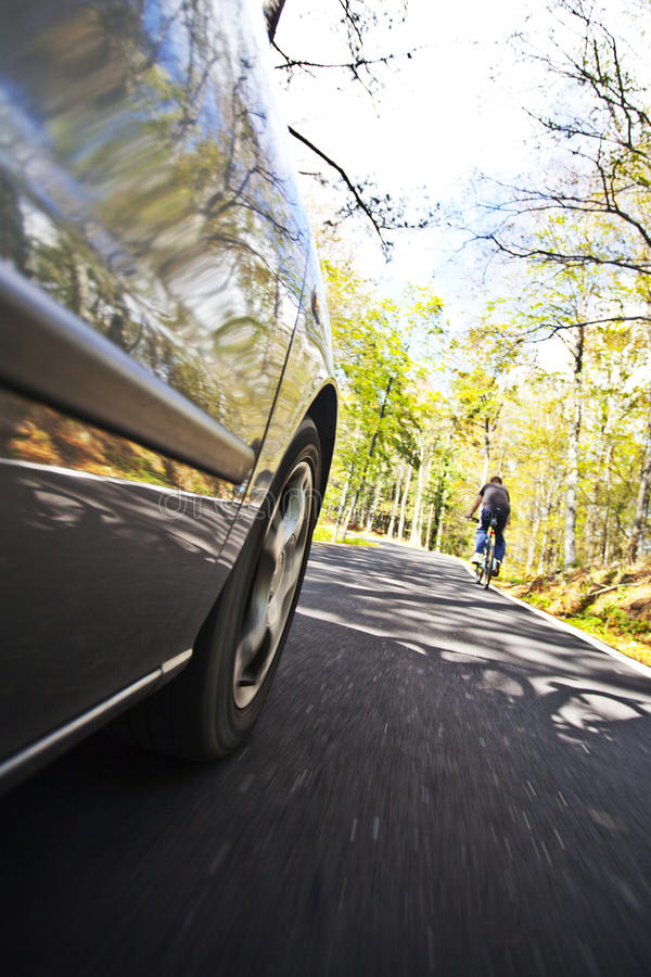 Bil och cyklist royaltyfri fotografi