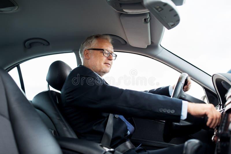 Bil och körning för lycklig hög affärsman startande royaltyfri foto