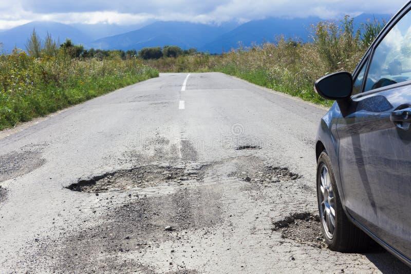 Bil och knäckt asfalt med hål royaltyfri fotografi