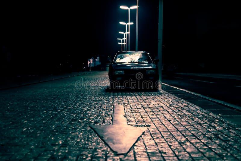 Bil på den lappade gatan med pilen som pekar i den mörka spöklika gatan, Zadar, Kroatien royaltyfria bilder