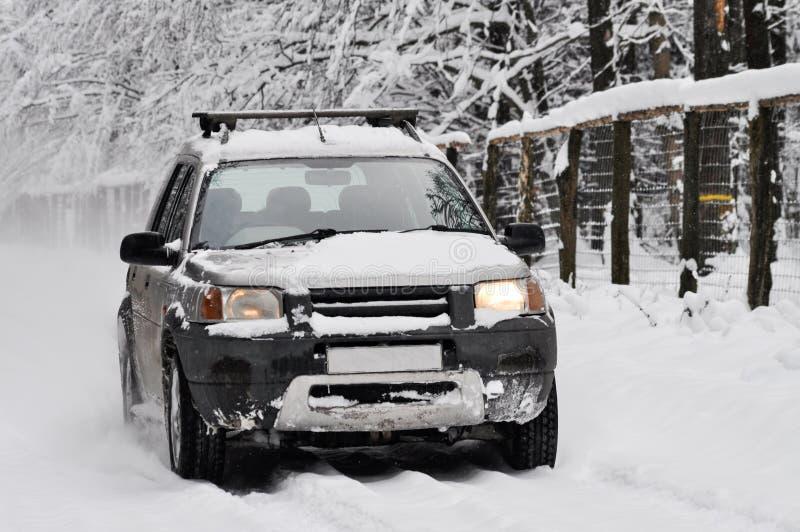 Bil på den snöig vägen i vinter arkivfoton