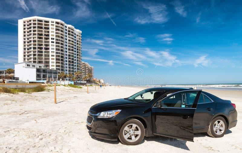 Bil på stranden, den Daytona Beach horisonten och oceanfronten ferie royaltyfri foto