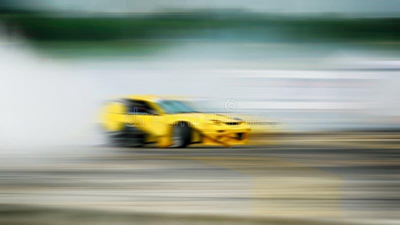 Bil som driver, sportbilhjul som driver och röker på suddiga lodisar royaltyfri fotografi