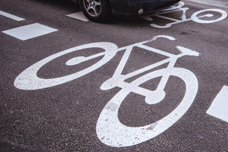 Bil som passerar över tecken för cykelgränd på vägen royaltyfri fotografi