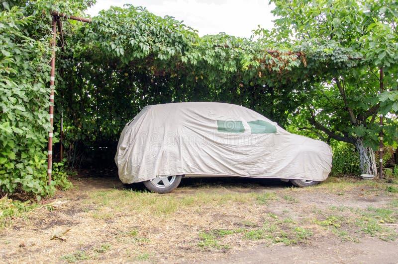Bil som täckas med en presenning för bilar royaltyfri foto