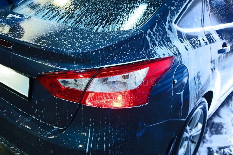 Bil som täckas med skum på biltvätt royaltyfri fotografi