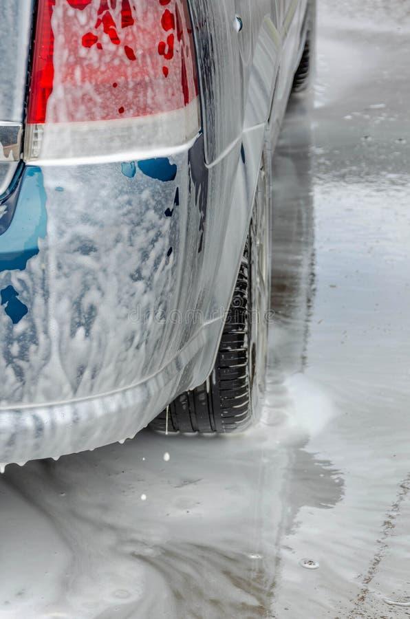 Bil som täckas med vitt skum på biltvättstation arkivfoton