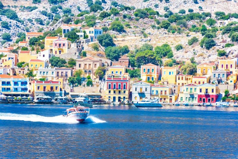 Bila fartyg och färgrika hus i hamnstad av den Symi Symi ön, Grekland fotografering för bildbyråer