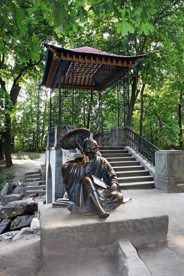 Bila Tserkva, Ukraine, 19 09 2009 zog eine Statue eines japanischen Sitzältesten nahe einem Japanisch-ähnlichen Gazebo Teehaus im lizenzfreie stockfotografie
