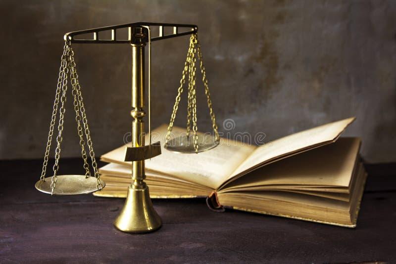 Bilancia della giustizia d'ottone d'annata e un vecchio libro su un woode marrone immagini stock