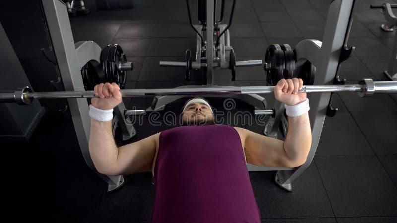 Bilanciere alzantesi maschio grassottello, piano personale di allenamento della palestra, desiderio di essere forte fotografie stock libere da diritti