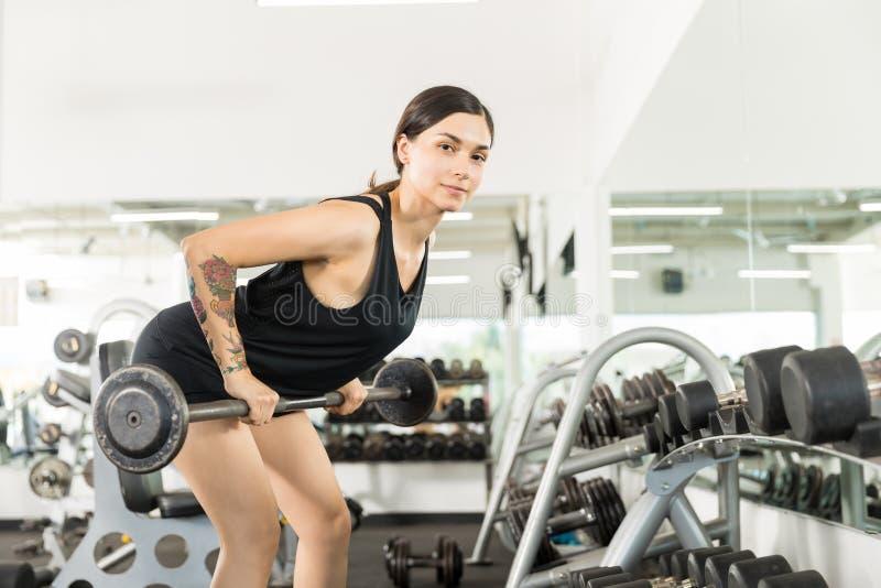 Bilanciere di Doing Bent Over Row Exercise With dell'atleta in palestra immagine stock
