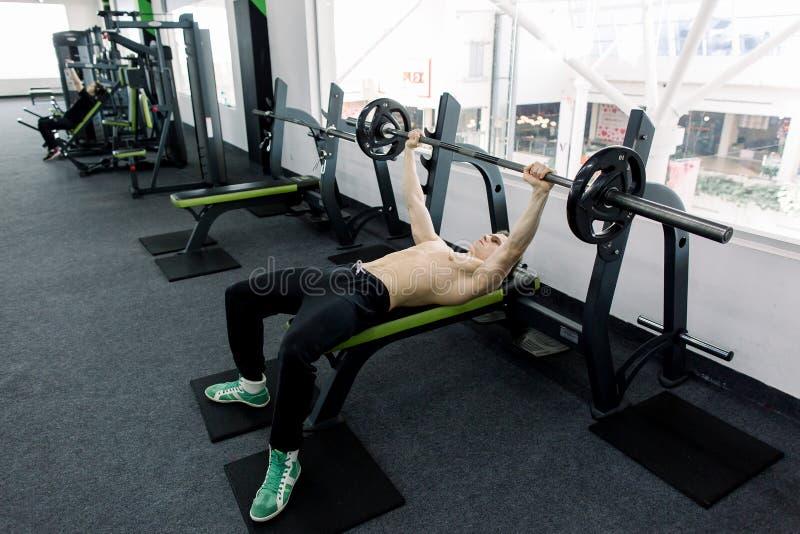 Bilanciere di sollevamento del giovane uomo caucasico muscolare sul banco nella palestra fotografia stock
