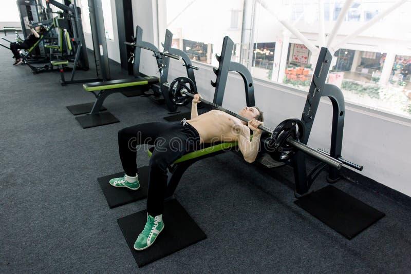 Bilanciere di sollevamento del giovane uomo caucasico muscolare sul banco nella palestra immagini stock
