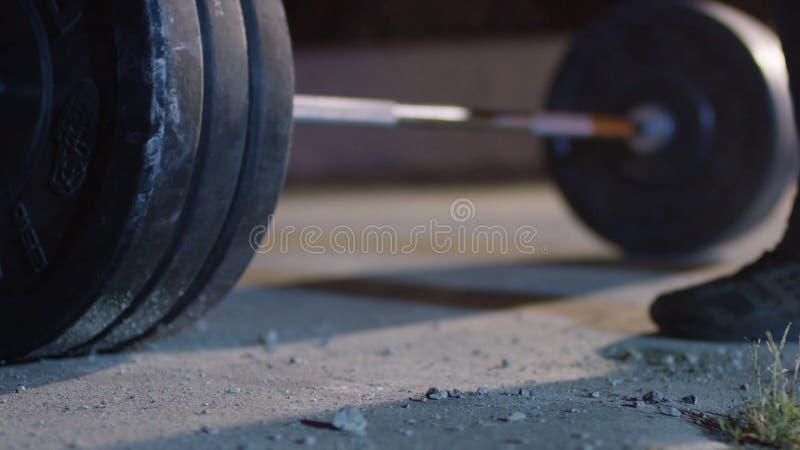 Bilanciere per i concorsi del powerlifter dell'atleta del piede e del deadlift nel powerlifting Giovane atleta che si prepara per immagine stock