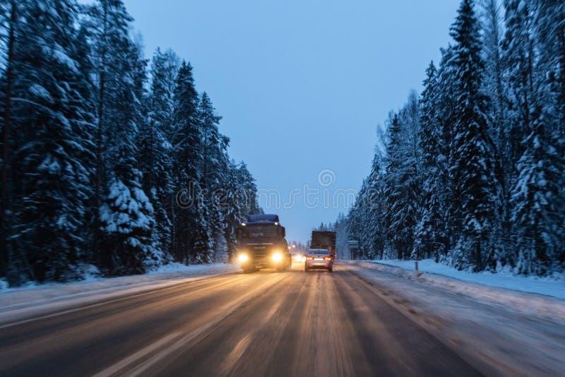 Bilar k?r med billyktor p? vinterv?gen i en sn?storm i skymningen, n?r sn? skulle flyga Begrepp av k?rning in royaltyfri foto