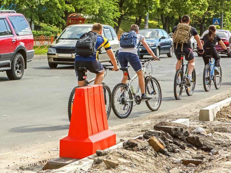 Bilar och cyklar på en stenlagd väg arkivfoto