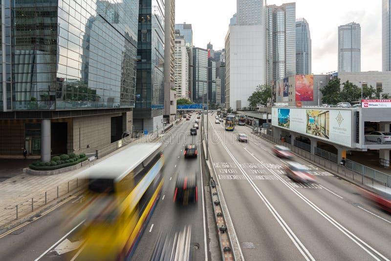 Bilar och g?ngare p? gataplats av trafik p? centrala Hong Kong Business Downtown District royaltyfri foto