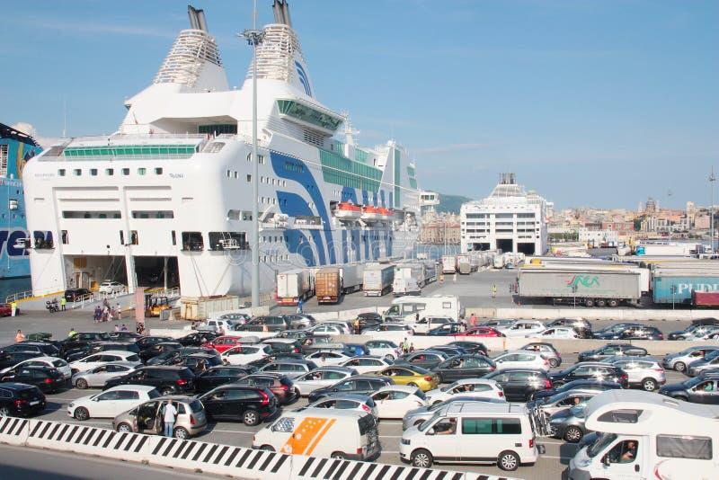 Bilar och passagerare som går ombord på en färja i porten av Genoa Italy royaltyfri foto