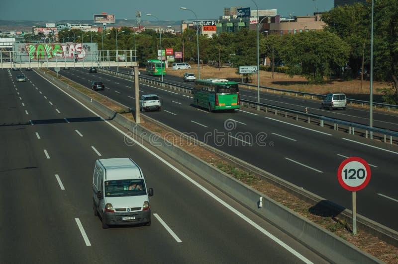 Bilar och skåpbil på huvudvägen och HASTIGHETSBEGRÄNSNINGvägvisare i Madrid arkivfoto